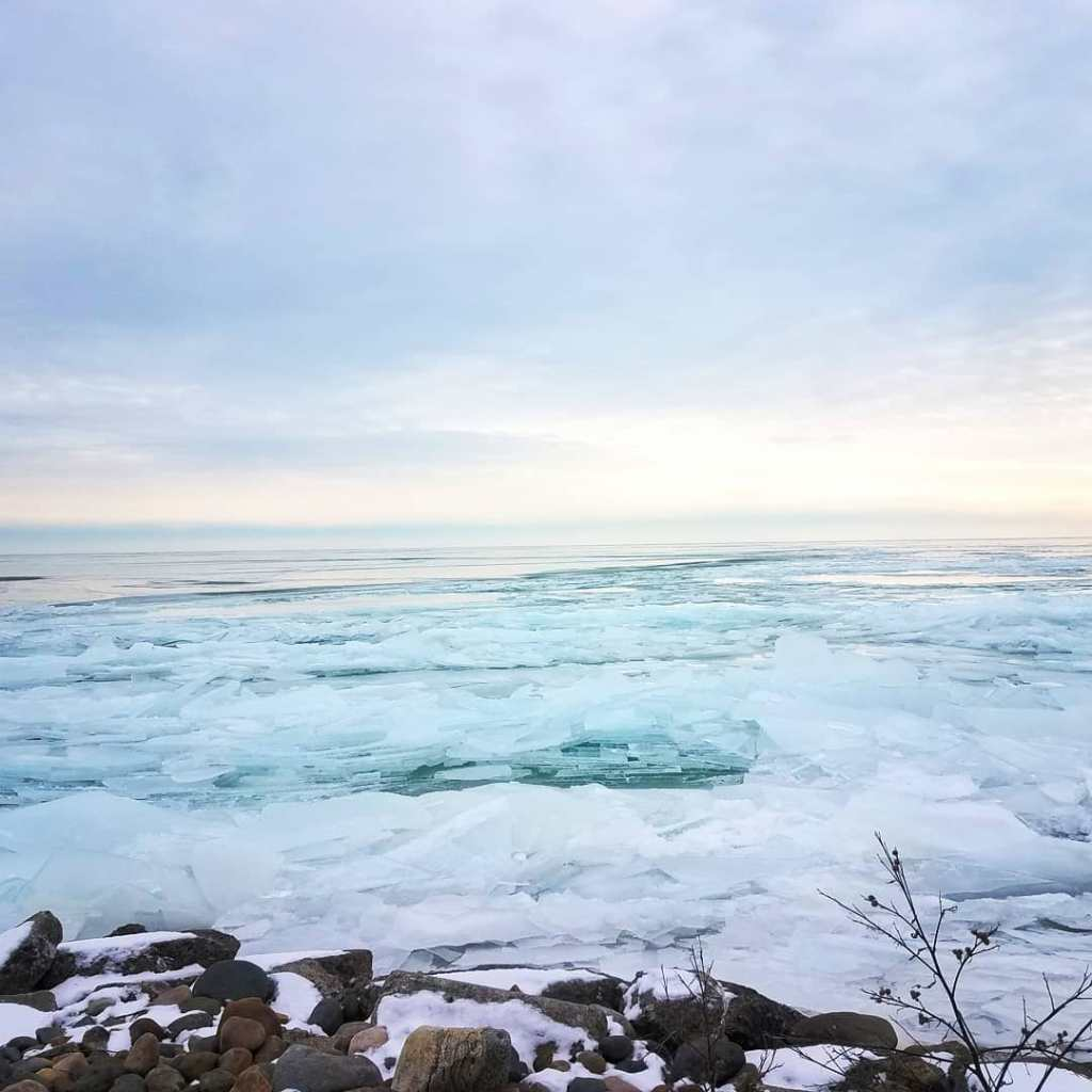 A picture of Lake St.Clair taken back in February 2020. The lake is mostly frozen. Ice covers the surface in chunks. The sky is a pale blue mixed with yellows and yellow-orange hues in a muted tone.