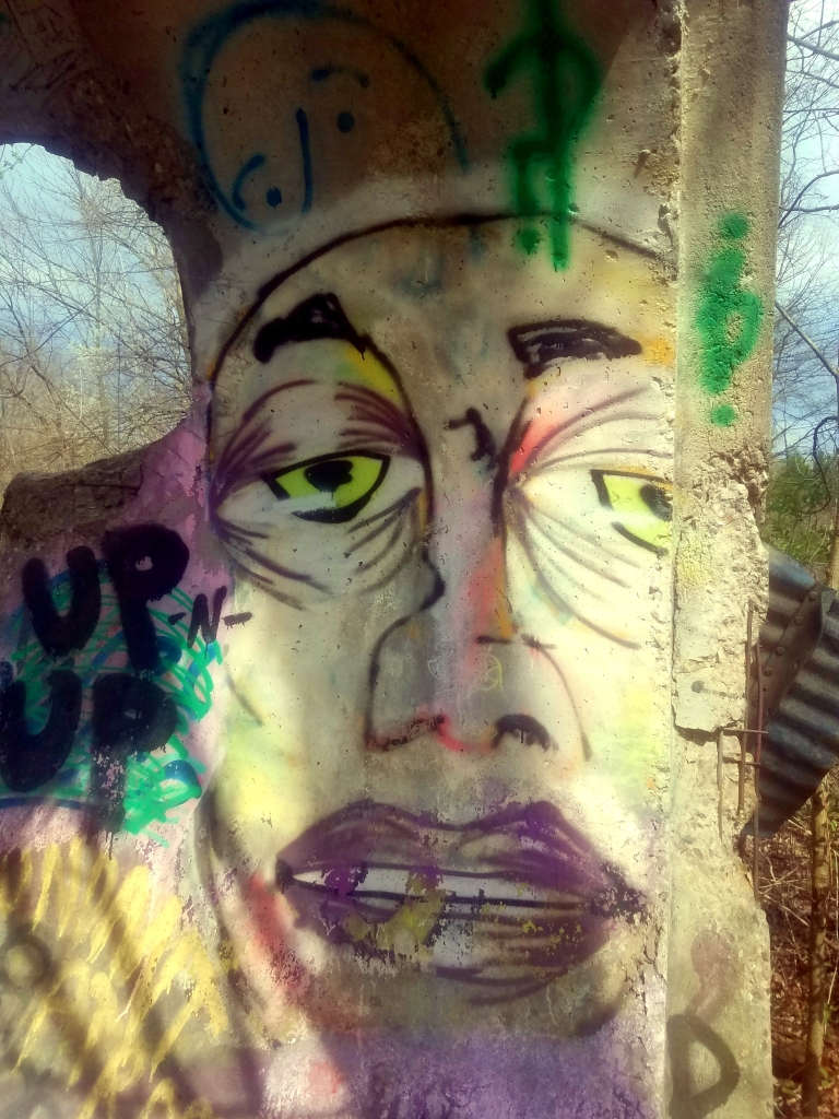 graffiti found on the Inwood Trails. The art depicts a face with tired eyes and which contrasts against the vibrate purple lipstick. The eyes are a neon yellow-green color.