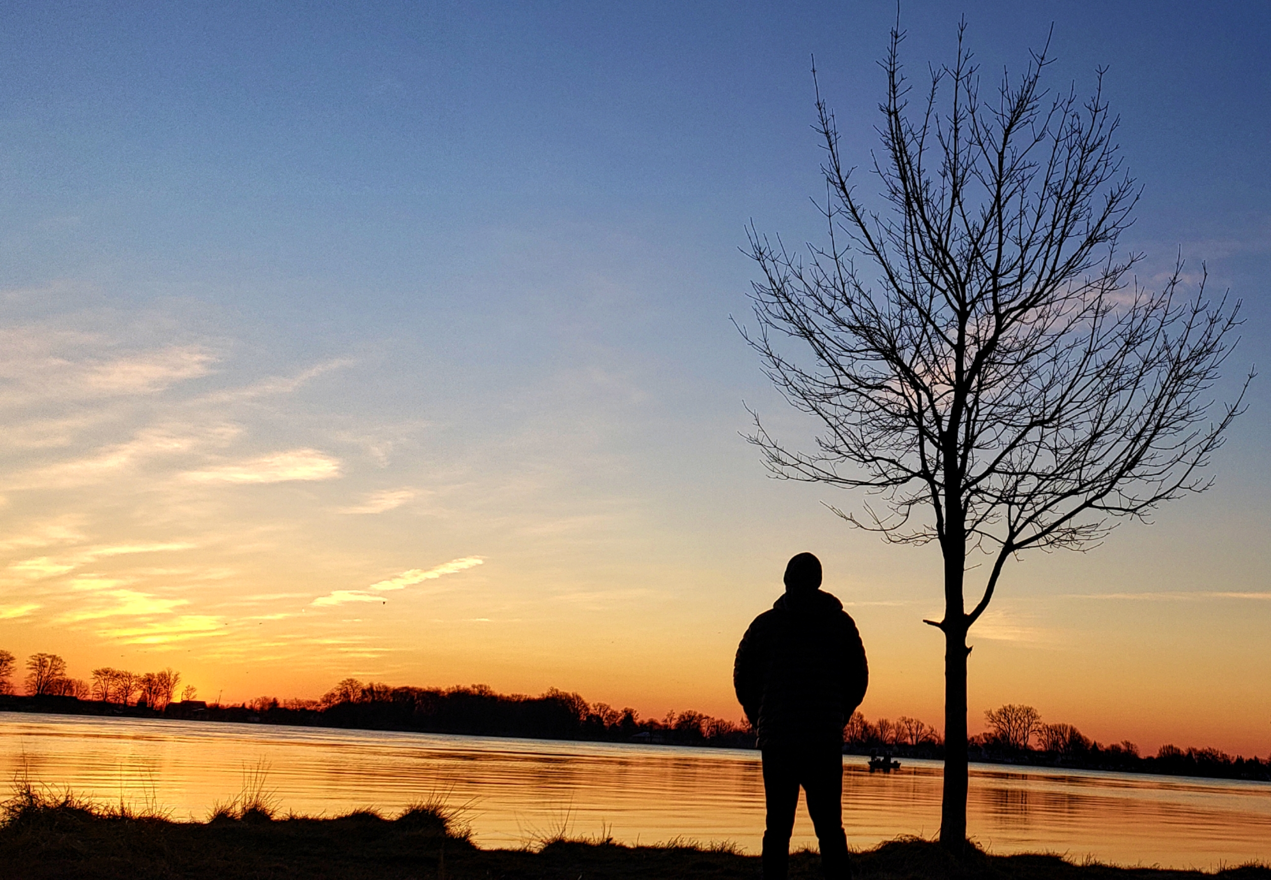 A silhouette of a man as he watcjrs the sun rise over the St.Clair River.