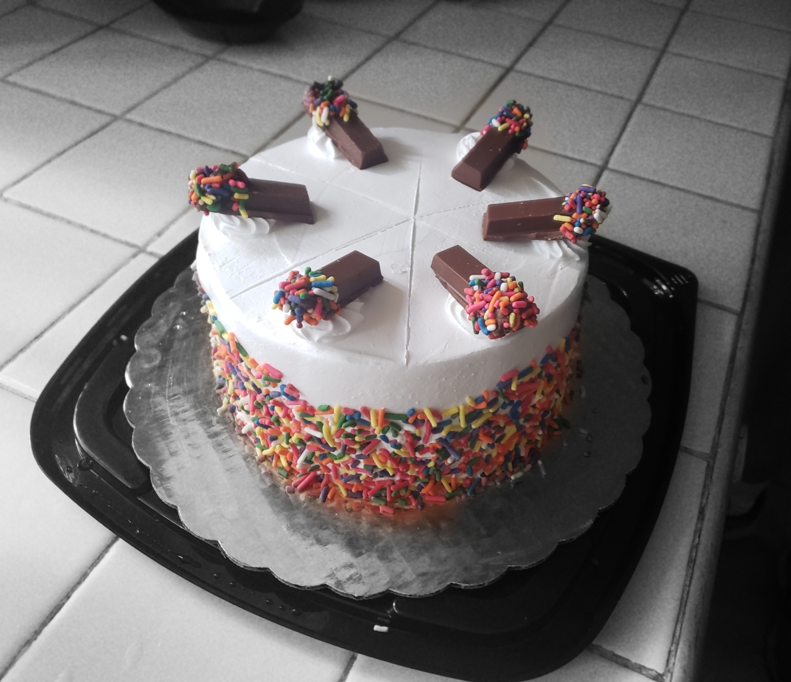 A cake with rainbow sprinkles sots on a counter, waiting to be devoured. The cake is topped with chocolate wafer candies that also have rainbow sprinkles.