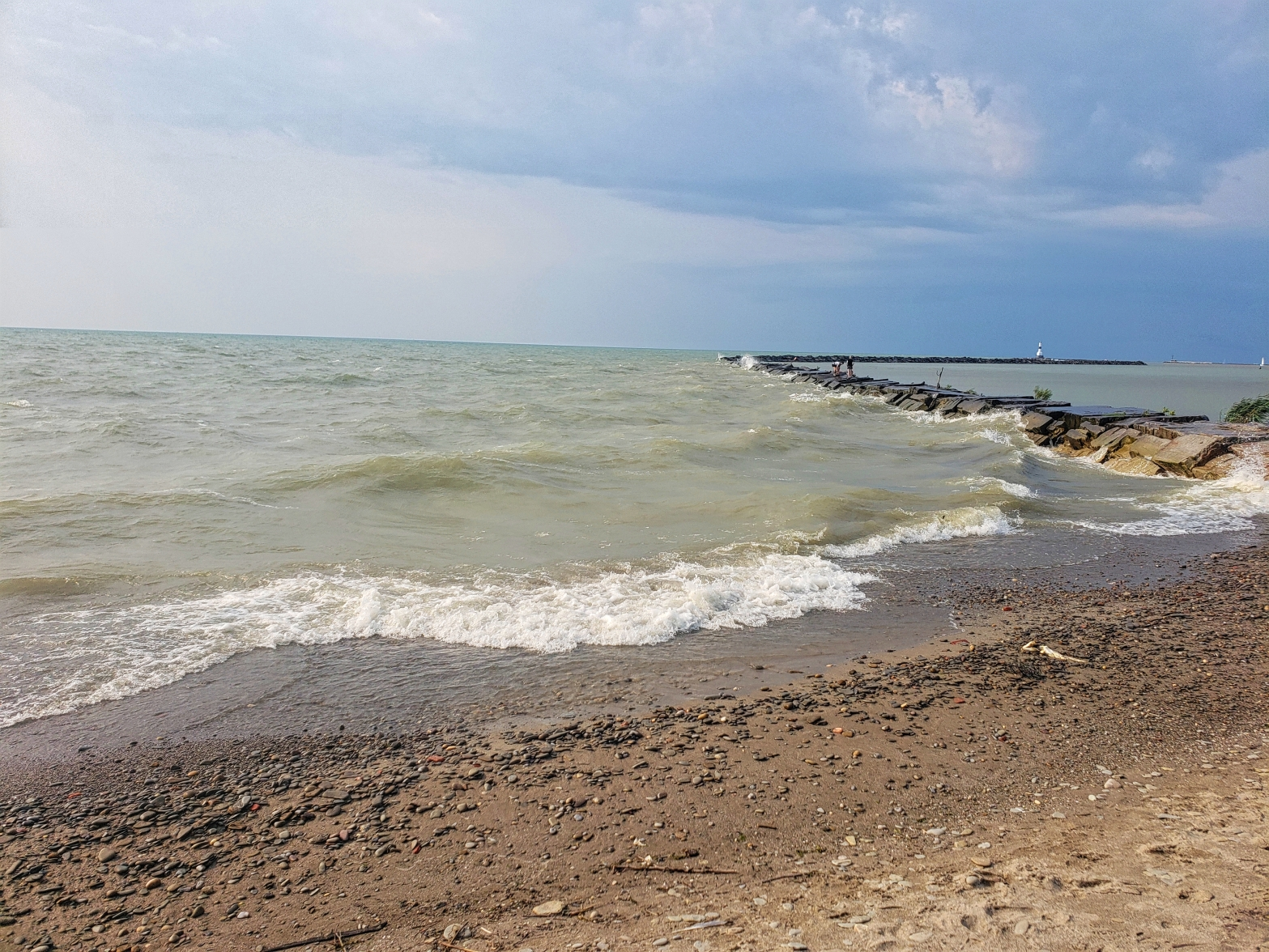 Waves of water crashing onto the beach of Conneaut Township Park