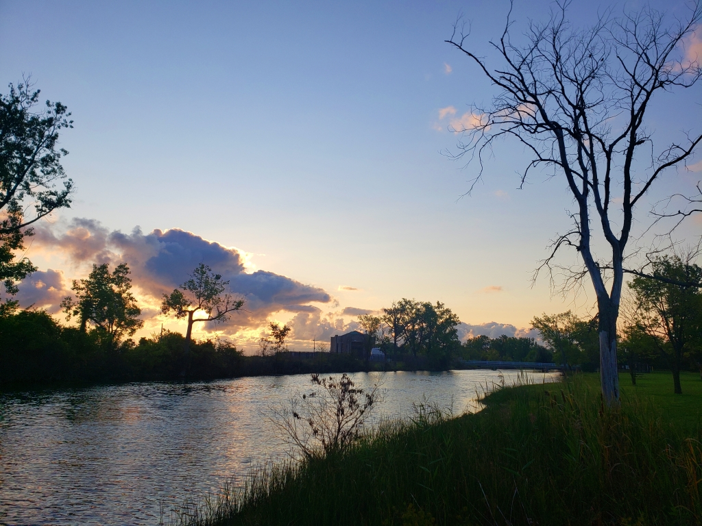the sun is rising in the sky along the Blue Heron Lagoon Trail at Belle Isle State Park