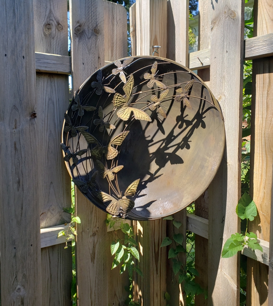 A decorative medallion hangs on a wooden fence in a backyard.