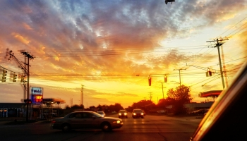 The sun is rising off in the distance across a busy intersection.